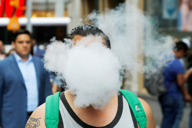 A man uses a vape as he walks on Broadway in New York City, U.S., September 9, 2019. (Photo by Andrew Kelly/Reuters)