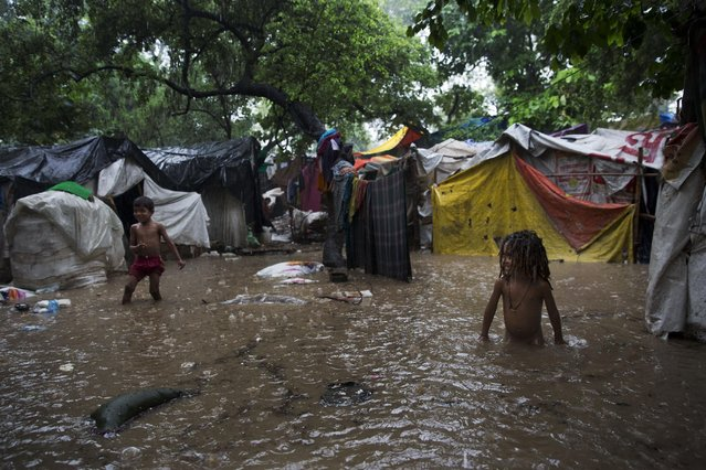 Indian children walk through a flooded slum area in New Delhi, India, Saturday, July 11, 2015. India receives the annual monsoon rains from June to September. (Photo by Bernat Armangue/AP Photo)
