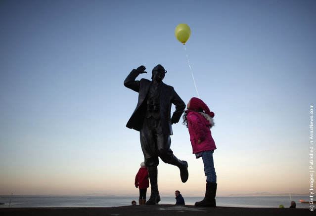 Children with balloons play beside the statue of British comedy legend Eric Morecambe