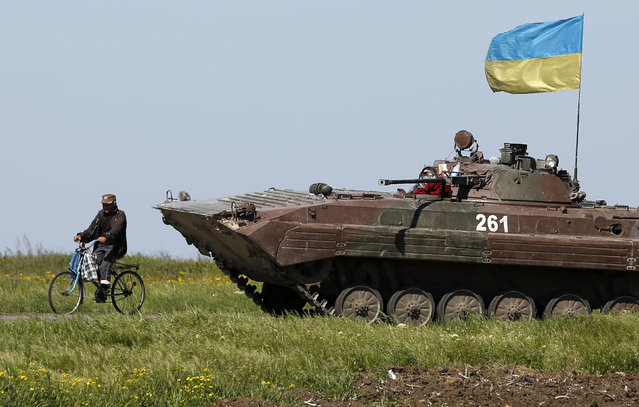 A man rides a bike past a Ukrainian armoured personnel carrier at a checkpoint in Mariupol, eastern Ukraine May 7, 2014. Ukrainian forces seized the rebel-held city hall in the eastern port city of Mariupol overnight, driving out pro-Russian activists, then withdrew, making no attempt to hold onto the building, witnesses said on Wednesday. (Photo by Marko Djurica/Reuters)
