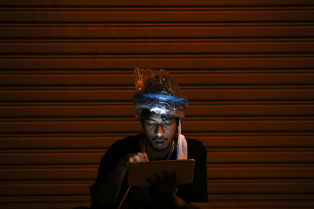 An anti-government protester wears a plastic bag over his head for protection against tear gas as he uses a tablet near the Government house, the site of clashes between protesters and police forces in Bangkok December 2, 2013. (Photo by Damir Sagolj/Reuters)