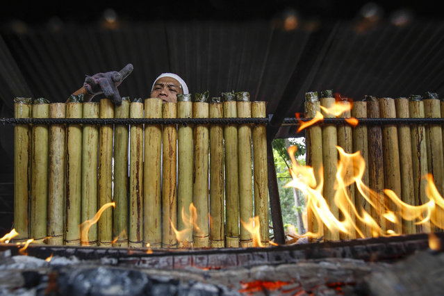 A Malaysian Muslim vendor cooks lemang, glutinous rice stuffed in bamboo sticks and cooked over a charcoal fire, ahead of the Eid Al-Fitr celebrations in Kuala Lumpur, Malaysia, Wednesday, July 15, 2015. The Eid Al-Fitr, one of the holiest religious practices, is celebrated with prayers and family reunions and other festivities among Muslims all over the world. (Photo by Joshua Paul/AP Photo)