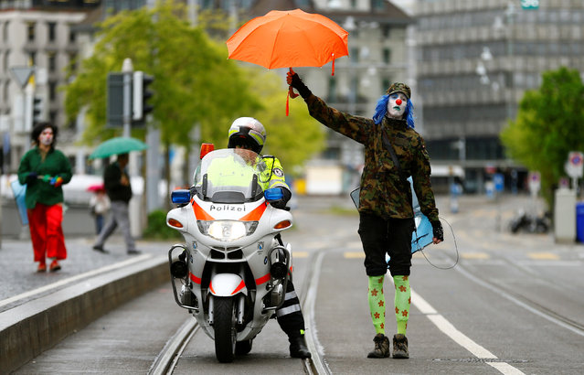 A protester dressed as a clown holds an umbrella over a Swiss police officer on a motorbike during a May Day demonstration in Zurich, Switzerland on May 1, 2017. (Photo by Arnd Wiegmann/Reuters)