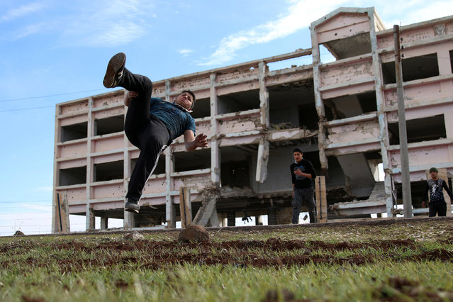 Ibrahim Eid, 16, demonstrates his Parkour skills in front of damaged building in the rebel-held city of Inkhil, west of Deraa, Syria, February 4, 2017. (Photo by Alaa Al-Faqir/Reuters)