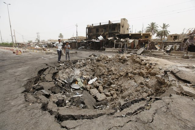 Men look at the site of Friday's suicide car attack at a market in Khan Bani Saad, northeast of Baghdad, July 18, 2015. More than 100 people were killed in the suicide car bombing at the busy market in the Iraqi town on Friday, in one of the deadliest attacks carried out by Islamic State militants since they overran large parts of the country. (Photo by Ahmed Saad/Reuters)