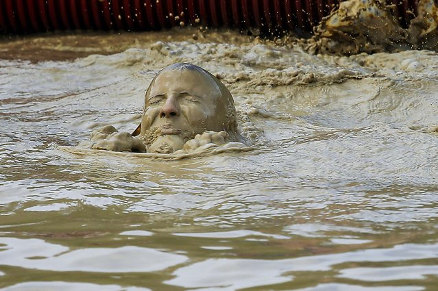 A participant dives into the muddy water as she makes her way through an obstacle course run in Weeze, Germany, on May 17, 2014. The goal is for participants  on the military designed track is to reach the finish line as a team. (Photo by Frank Augstein/Associated Press)