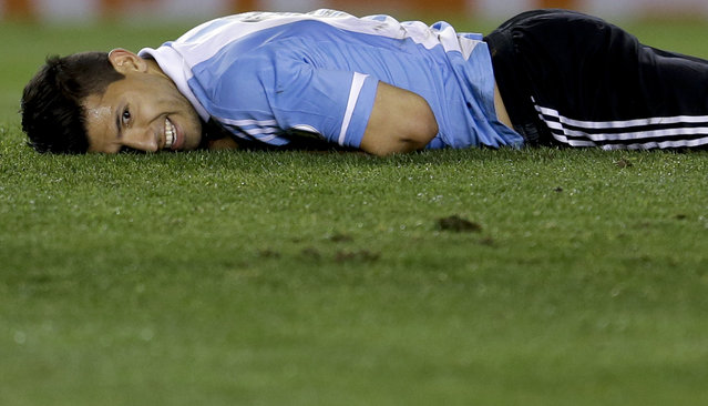 Argentina's Sergio Aguero smiles after falling on the pitch during a 2014 World Cup qualifying soccer match against Peru in Buenos Aires, Argentina, October 11, 2013. (Photo by Natacha Pisarenko/AP Photo)