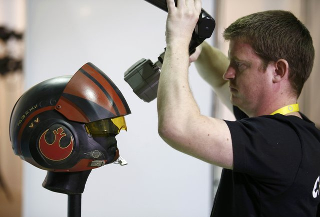 "A technician laser-scans a replica of Poe Dameron's helmet from ""Star Wars: The Force Awakens"", in the Propshop headquarters at Pinewood Studios near London, Britain May 25, 2016. (Photo by Peter Nicholls/Reuters)"