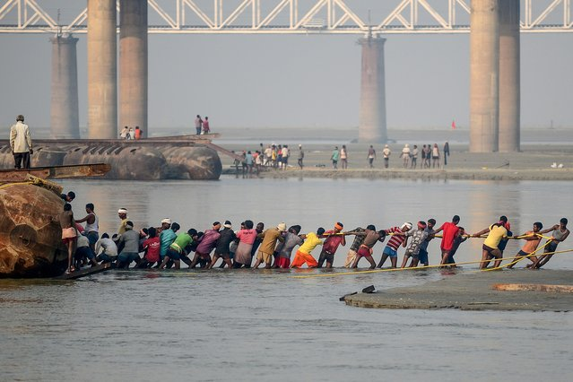 Labourers pull a pontoon buoy with ropes in the Ganges river as they build a floating pontoon bridge for the upcoming Hindu festival of Magh Mela in Allahabad on November 26, 2019. (Photo by Sanjay Kanojia/AFP Photo)