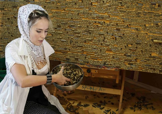 Ukrainian artist Dariya Marchenko works in her studio at pictures consisting of cartridges brought from the frontline in eastern Ukraine, in Kiev, July 22, 2015. (Photo by Gleb Garanich/Reuters)