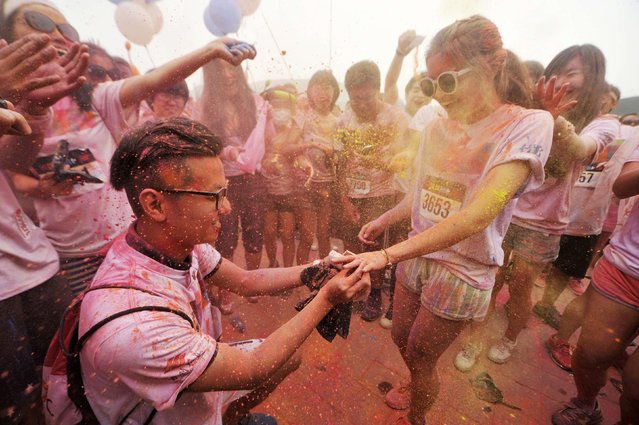 A man (bottom L) propose to his girlfriend as they are sprayed with colour powder during a five-kilometre colour run event in Beijing June 21, 2014. (Photo by China Daily/Reuters)