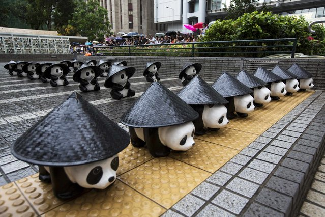 Papier-mache pandas, created by French artist Paulo Grangeon, are covered with conical hats as they are displayed under the rain at the financial Central district in Hong Kong June 21, 2014. (Photo by Tyrone Siu/Reuters)