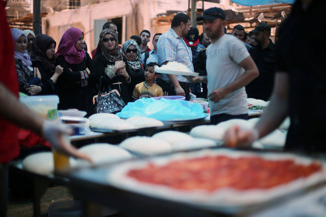 Palestinians watch the preparation of pizzas by an Italian chef during a food and cultural exchange event at the seaport of Gaza City June 1, 2016. (Photo by Ibraheem Abu Mustafa/Reuters)