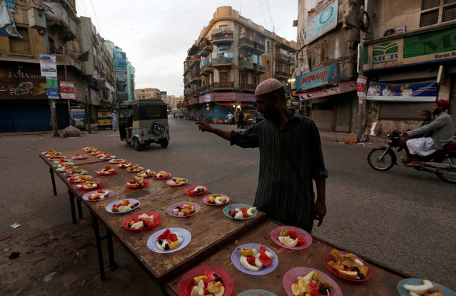A man counts the number of plates set out on a street side for passers by to be able to break fast on the first day of the Muslim holy month of Ramadan in Karachi, Pakistan June 7, 2016. (Photo by Akhtar Soomro/Reuters)