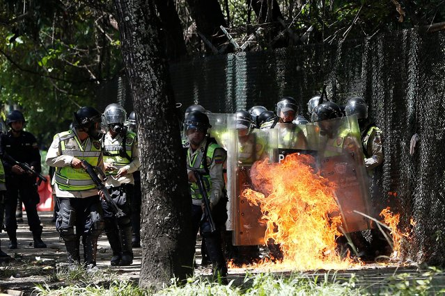 A molotov cocktail explodes in front of riot police officers as they clash with demonstrators during a protest called by university students against Venezuela's government in Caracas, Venezuela, June 9, 2016. (Photo by Carlos Garcia Rawlins/Reuters)