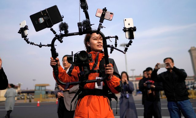"""A media reporter uses mobile phones to do live broadcasts during the second plenary session of the 13th National People's Congress (NPC) outside the Great Hall of the People (GHOP) in Beijing, China, 08 March 2019. The NPC has over 3,000 delegates and is the world's largest parliament or legislative assembly though its function is largely as a formal seal of approval for the policies fixed by the leaders of the Chinese Communist Party. The NPC runs alongside the annual plenary meetings of the Chinese People's Political Consultative Conference (CPPCC), together known as """"Lianghui"""" or """"Two Meetings'"""". (Photo by Wu Hong/EPA/EFE)"""