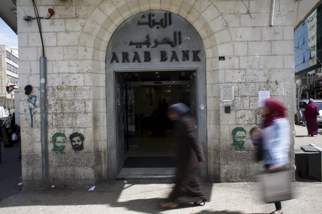 Palestinians walk past a bank in the West Bank city of Ramallah March 25, 2015. (Photo by Mohamad Torokman/Reuters)
