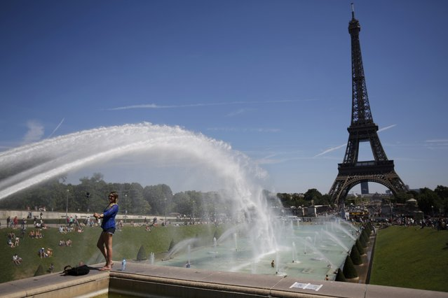 A tourist makes a selfie in front of the Eiffel Tower in Paris, France, August 2, 2015 as warm summer temperatures return to the French capital. (Photo by Stephane Mahe/Reuters)