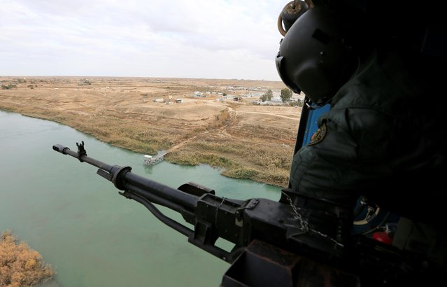 A member of Iraqi security forces is seen in a helicopter during military operations to search for Islamic State militants in Anbar province, Iraq on December 29, 2019. (Photo by Thaier Al-Sudani/Reuters)