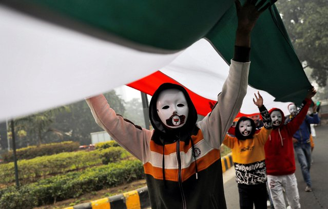 Demonstrators wearing masks hold a tricoloured flag in front of the India Gate during a demonstration against what they say was an alleged police action conducted during recent protests against a new citizenship law, in New Delhi, December 30, 2019. (Photo by Adnan Abidi/Reuters)