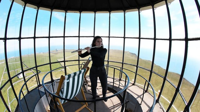 """Carolyn Byrne, a lawyer from Manhattan, plays her flute at the top of the """"Old Light"""" lighthouse during the Cloud Appreciation Society's gathering in Lundy, Britain, May 19, 2019. (Photo by Phil Noble/Reuters)"""