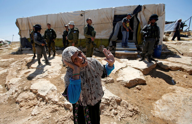 An old Palestinian woman reacts as Israeli troops demolish sheds belonging to Palestinians near the West Bank village of Yatta, south of Hebron June 19, 2016. (Photo by Mussa Qawasma/Reuters)