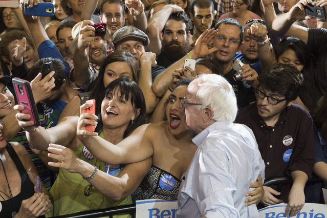 Naomi Scott, center, of McMinnville, Ore., takes a picture with Democratic presidential candidate Sen. Bernie Sanders, I-Vt., at a rally, Sunday, August 9, 2015, at the Moda Center in Portland, Ore. (Photo by Troy Wayrynen/AP Photo)