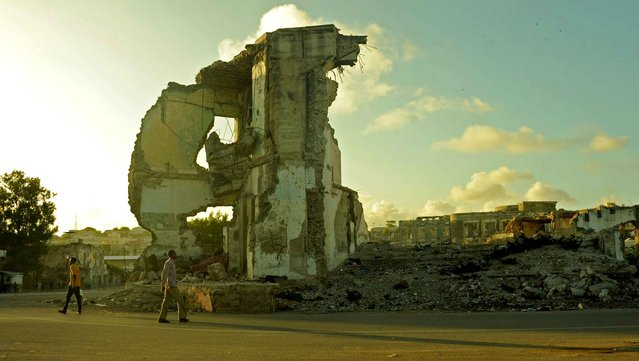 A man walks past the ruins of a building as the sun sets on August 11, 2015 in Mogadishu. (Photo by Mohamed Abdiwahab/AFP Photo)