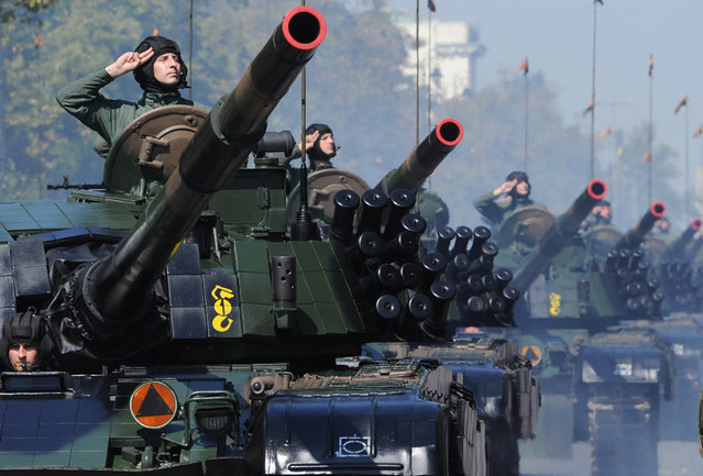 Polish army soldiers salute as tanks roll on one of the city's main streets during a military parade celebrating the Polish Army Day in Warsaw, Poland, Saturday, August 15, 2015. (Photo by Alik Keplicz/AP Photo)