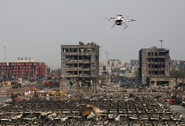 A drone operated by paramilitary police flies over the site of last week's explosions at Binhai new district in Tianjin, China, August 17, 2015. (Photo by Kim Kyung-Hoon/Reuters)