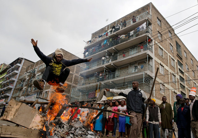 A demonstrator jumps over a barricade set on fire in Mathare, in Nairobi, Kenya August 9, 2017. (Photo by Thomas Mukoya/Reuters)
