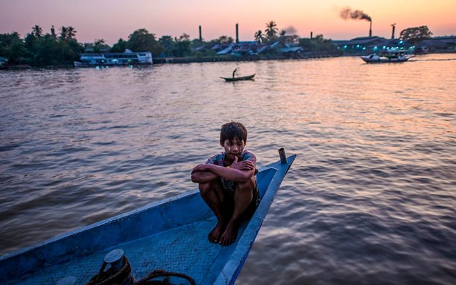 This photo taken on December 6, 2019 shows a boy sitting on a boat at a pier in Mawgyun of Irrawaddy region. (Photo by Ye Aung Thu/AFP Photo)