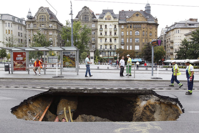 A hole in the road following a storm the day before on Fovam square in Budapest, Hungary, 18 August 2015. The storm that hit 17 August brought more rain than the average for the whole month of August. (Photo by Zsolt Szigetvary/EPA)