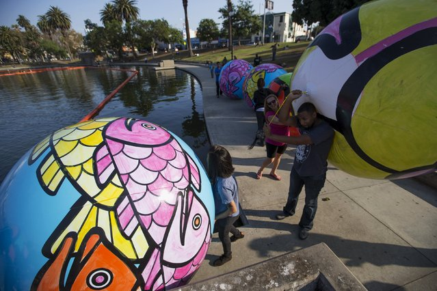 "Volunteers carry inflated spheres to be lowered into MacArthur Park Lake during the installation of Portraits of Hope's exhibition ""Spheres at MacArthur Park"" in Los Angeles, California August 21, 2015. (Photo by Mario Anzuoni/Reuters)"