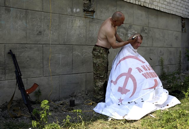 An Ukrainian serviceman from the Donbass volunteer battalion is covered with a Ukrainian Communist Party flag as he gets a hair cut on August 4, 2014 in eastern Ukrainian city of Popasna, Lugansk region, freed by Ukrainian forces from pro-Russian militants. (Photo by Anatolii Stepanov/AFP Photo)