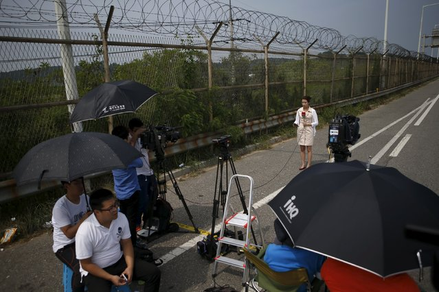 A reporter prepares for a report at a checkpoint on the Grand Unification Bridge which leads to the truce village Panmunjom, just south of the demilitarized zone separating the two Koreas, in Paju, South Korea, August 24, 2015. (Photo by Kim Hong-Ji/Reuters)