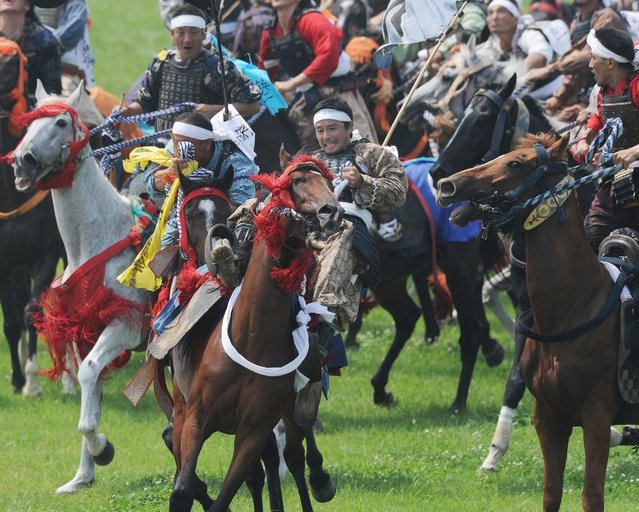 """A local man (C) in samurai armor falls off his horse as he tries to catch a yellow sacred flag at the annual Soma Nomaoi Festival in Minamisoma, Fukushima Prefecture, on July 29, 2012. Some 400 horses and thousands of people took part in the 1,000-year-old """"Soma Nomaoi"""", or wild horse chase, at the weekend in the shadow of Japan's crippled Fukushima nuclear plant. (Photo by Toru Yamanaka/AFP Photo)"""