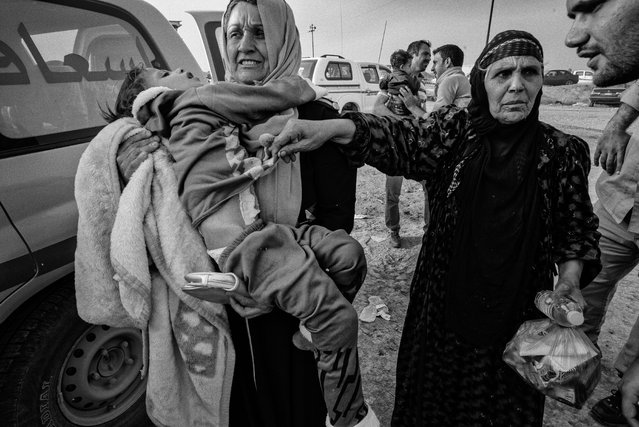 Distraught families with children injured in a landmine blast as they fled the front line are seen in Gogjali, east of Mosul, in 2016. (Photo by Sean Sutton for the Mines Advisory Group/The Guardian)