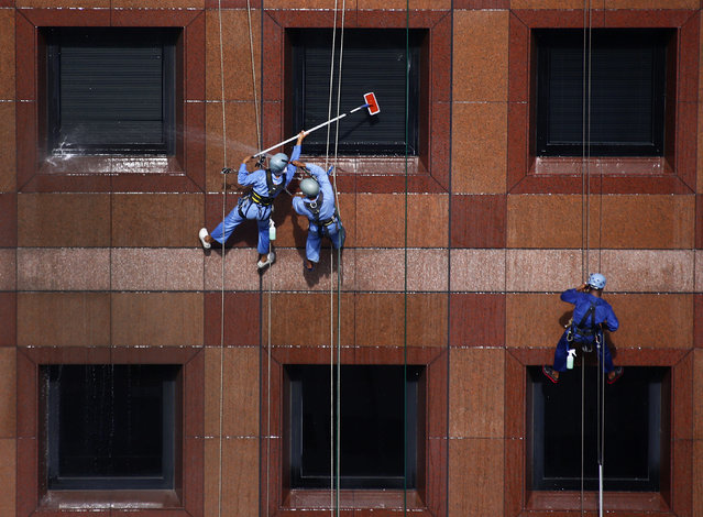 Window cleaners hang from the facade of Ngee Ann City shopping mall in Singapore January 9, 2014. (Photo by Petar Kujundzic/Reuters)