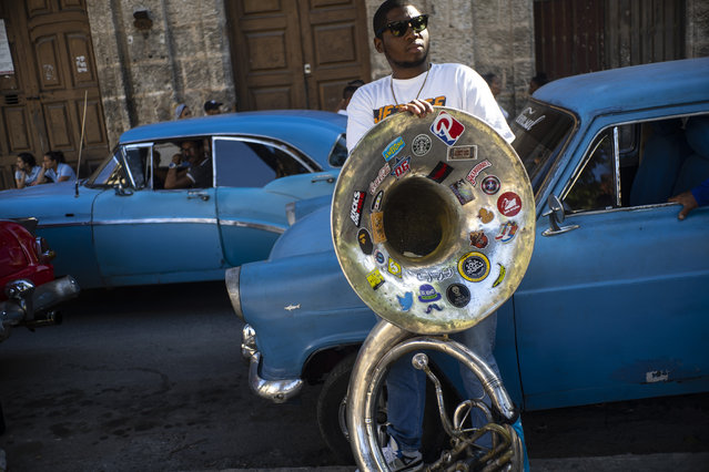 A member of the The Soul Rebels Band from New Orleans waits on a classic American car that starts the music conga through the streets of Old Havana within the activities of the 35th Havana Jazz Plaza festival in Havana, Cuba, Wednesday, January 15, 2020. (Photo by Ramon Espinosa/AP Photo)