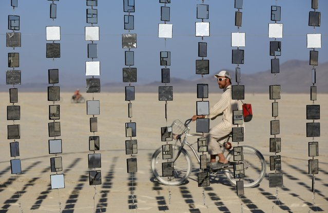 """Austin Cable rides past an art installation during the Burning Man 2015 """"Carnival of Mirrors"""" arts and music festival in the Black Rock Desert of Nevada, August 31, 2015. (Photo by Jim Urquhart/Reuters)"""