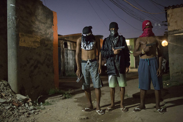 In this July 11, 2016 photo, young drug traffickers pose for photos holding their guns at a slum in Rio de Janeiro, Brazil. Teenage boys openly tote guns as they run in flip-flops through a maze of alleys. When Associated Press journalists visit areas with authorization from the gangs, the ones who agree to be photographed cover their faces so they can't be identified. (Photo by Felipe Dana/AP Photo)