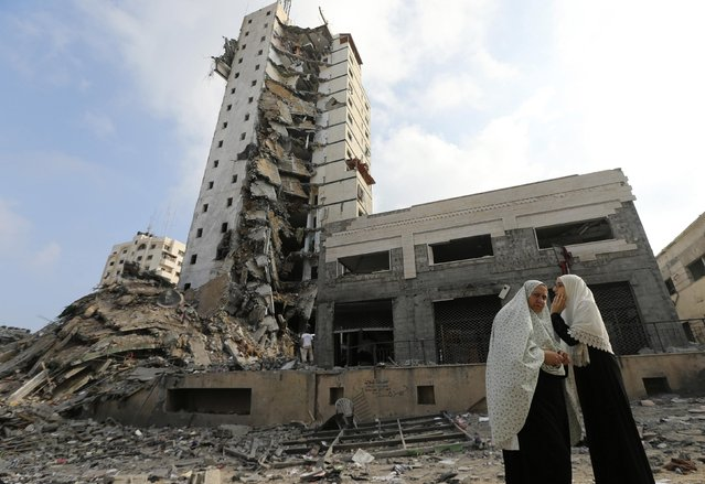 Palestinian women stand next to the remains of one of Gaza's tallest apartment towers, which witnesses said was hit by an Israeli air strike that destroyed much of it, in Gaza City August 26, 2014. (Photo by Mohammed Salem/Reuters)