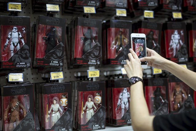 """A customer takes pictures of the new """"Star Wars: The Force Awakens"""" on """"Force Friday"""" in Hong Kong, China, September 4, 2015. (Photo by Tyrone Siu/Reuters)"""