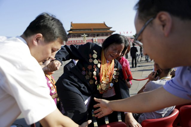 Shen Jilan wearing insignias and medals is helped to her seat, ahead of the military parade to mark the 70th anniversary of the end of World War Two, in Beijing, China, September 3, 2015. Shen, 85, is the only person in China to be elected 12 consecutive times as a member of China's parliament, after she was appointed to China's first National People's Congress (NPC) in 1954, according to local media. (Photo by Jason Lee/Reuters)