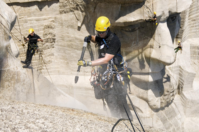 The team cleans Mount Rushmore. (Photo by Caters News Agency)