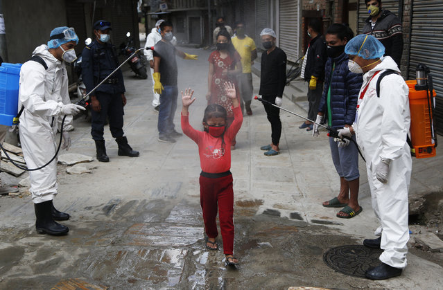 A young Nepalese girl is sprayed with disinfectants as she arrives to get free food distributed by social workers during lockdown to control the spread of the new coronavirus in Kathmandu, Nepal, Sunday, May 3, 2020. Nepal has extended the lockdown to May 7 and closure of the international border to May 13. (Photo by Niranjan Shrestha/AP Photo)