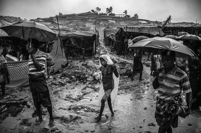A Rohingya refugee girl wears a plastic bag as she walks in the monsoon rains at the Palongkali refugee camp on September 19, 2017 in Cox's Bazar, Bangladesh. (Photo by Kevin Frayer/Getty Images)