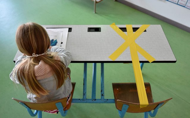 A pupil of the Sainte-Croix elementary school works as half of her writing desk is marked with a tape to ensure that safe distance is kept on May 15, 2020 in Hannut, as the lockdown introduced two months ago to fight the spread of the Covid-19 disease caused by the novel coronavirus is progressively easing. (Photo by John Thys/AFP Photo)