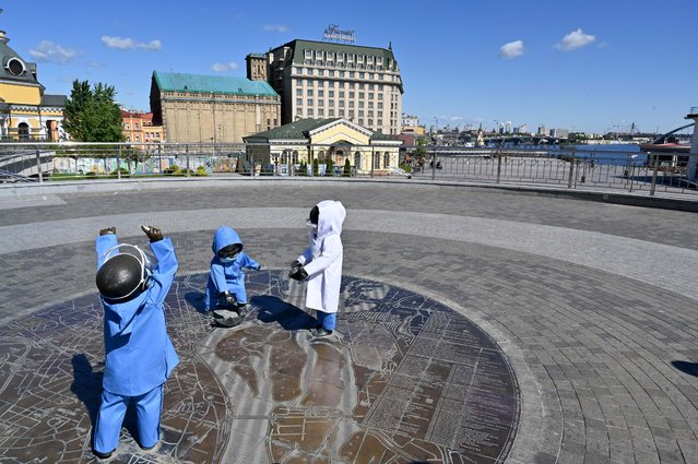 This picture shows personag's of monument for founders of Kiev, brothers Kyi, Shchek, Khoryv and heir sister Lybid who are depicted as small children by Sculptor Volodymyr Zhuravel Zhuravel, dressed in symbolic epidemiological suit in Kiev on May 13, 2020. The artist organized a cultural action-performance to support 3208 Ukrainian doctors and medical workers who were infected during fighting with spread of the novel coronavirus (Covid-19). (Photo by Sergei Supinsky/AFP Photo)